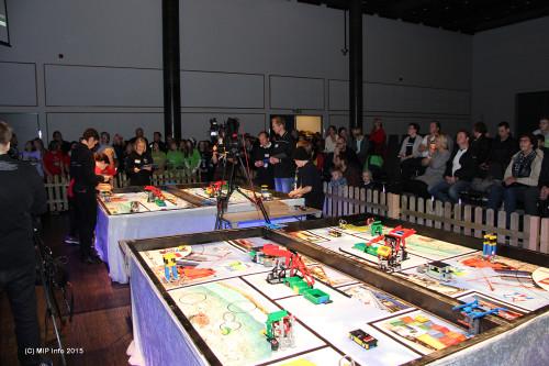 Konkurransebordet der lagene skulle vise sine ferdigheter i programmering og kjøring av roboten. Her er det et lag fra Korgen Lego Locos og et fra Nesna i aksjon, mens publikum følger spent med på storskjerm til venstre for lagene.