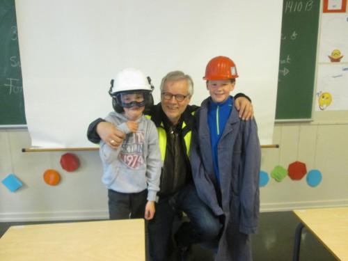 Ivar Hartviksen og to gutter, -en med ny hjelm med hørselvern og vernebriller og en med gammel jernverksfrakk og besøkshjelm.