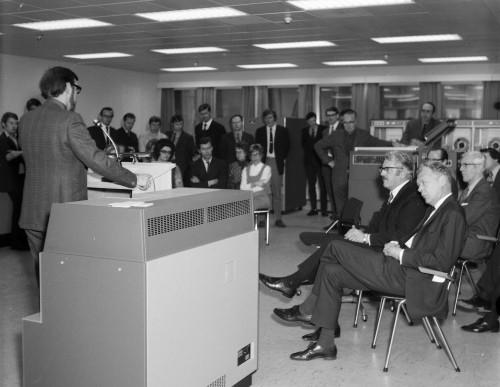 C. H. Devonald fra International Computers Ltd (ICL) står på talerstolen ved overleveringen av Jernverkets nye dataanlegg i 1972. I bakgrunn står de ansatte ved EDB-avdelingen, mens adm. Dir. Per Blidensol sitter i forkant, sammen med blant annet salgsdirektør Å. Laukholm fra Norsk Data og driftsdirektør Sven Edin.